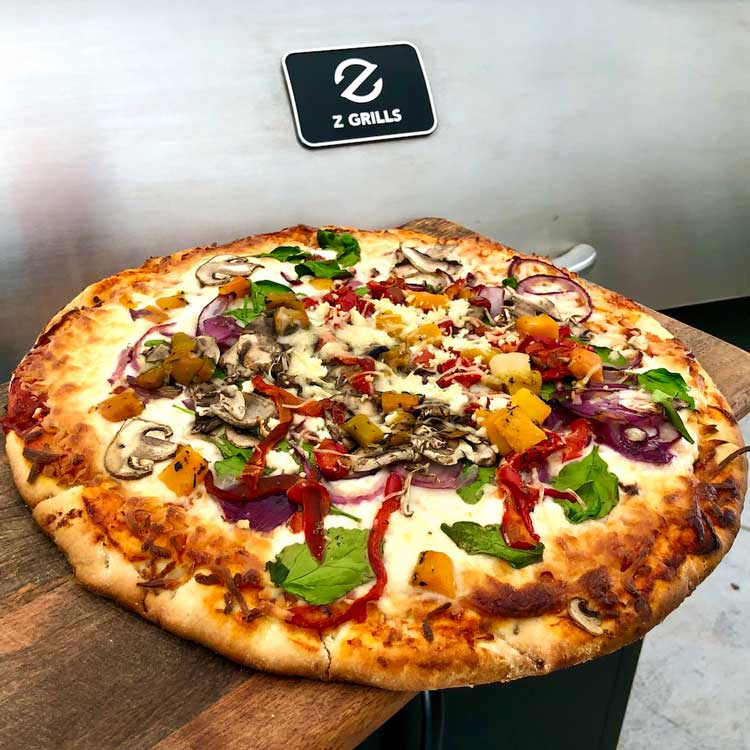 Cooked Pizza in front of a Z Grills 700E Wood Pellet Smoker Grill