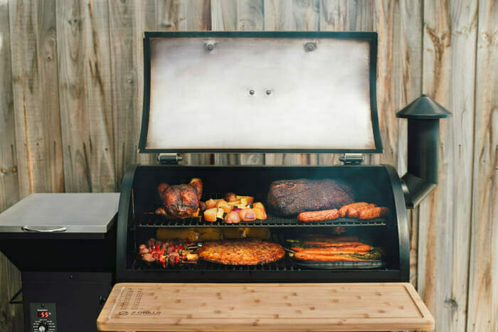 A variety of smoked food such as briskets, ribs, potatoes, carrots in a Z Grill pellet smoker
